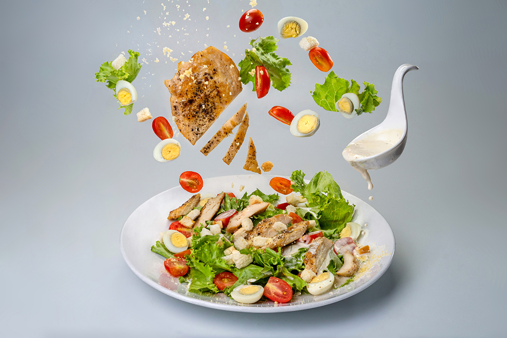 Salad with chicken, parmesan cheese, vegetables and saucespoon with flowing sauce in lavitation on light background. Banner menu recipe. Banner menu recipe.