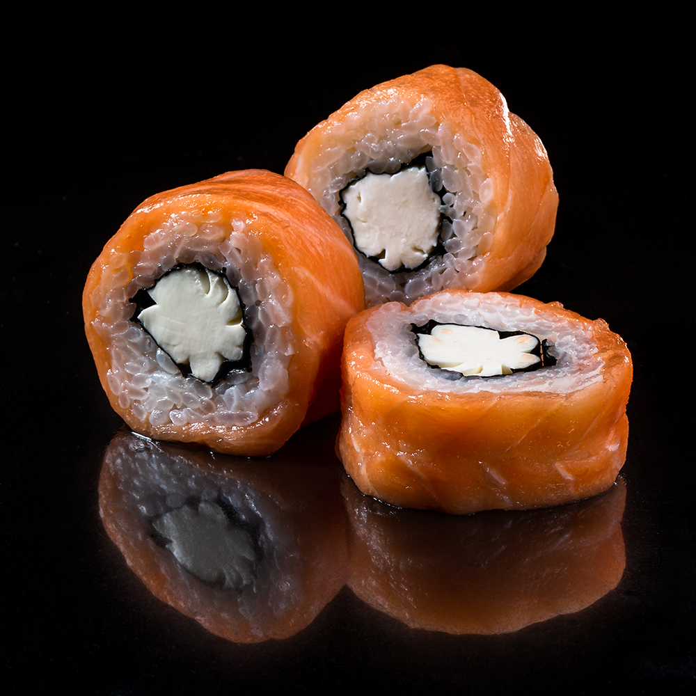 Closeup image of classic Philadelphia Sushi rolls with salmon and cream cheese over black background.