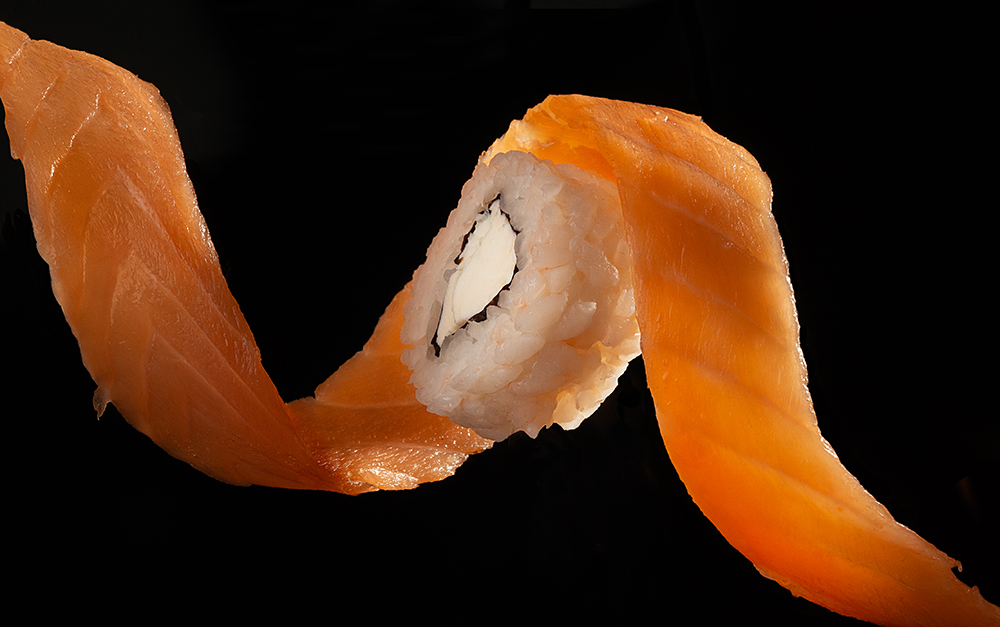 Salmon fillet in the form of a spiral wraps a Sushi roll with Philadelphia cheese  on a black background, bottom view
