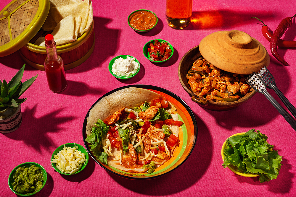 Spicy chicken, vegetables, sour cream, chees, guacamole, Enchilada Sauce and corn tortillas fajitas in bamboo pancake basket on a red background, top view. Delicious snack, tapas in mexican style