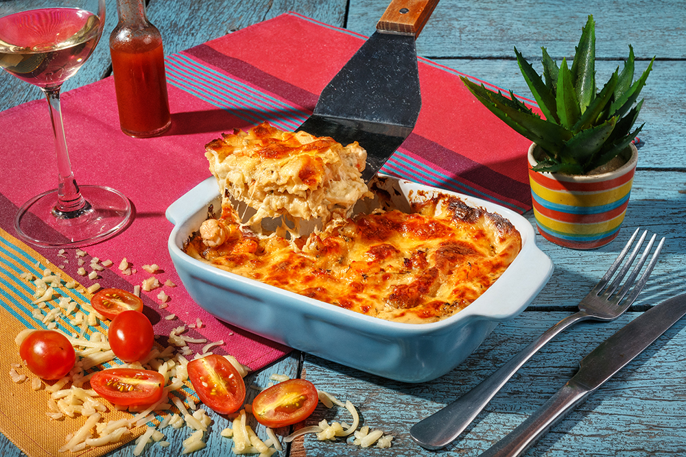 Traditional italian lasagna with vegetables, shrimps and cheese in a blue casserole dish and and part of dish on plate with overturned glass of wine on a pink and blue background.