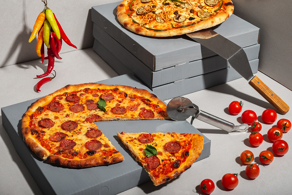Creative layout of hot delicious pizzas on grey background. Pizza pepperoni and vegetable pizza with pizza spatula and cutter, design or poster for promotions and discounts with copy space. Fast Food concept