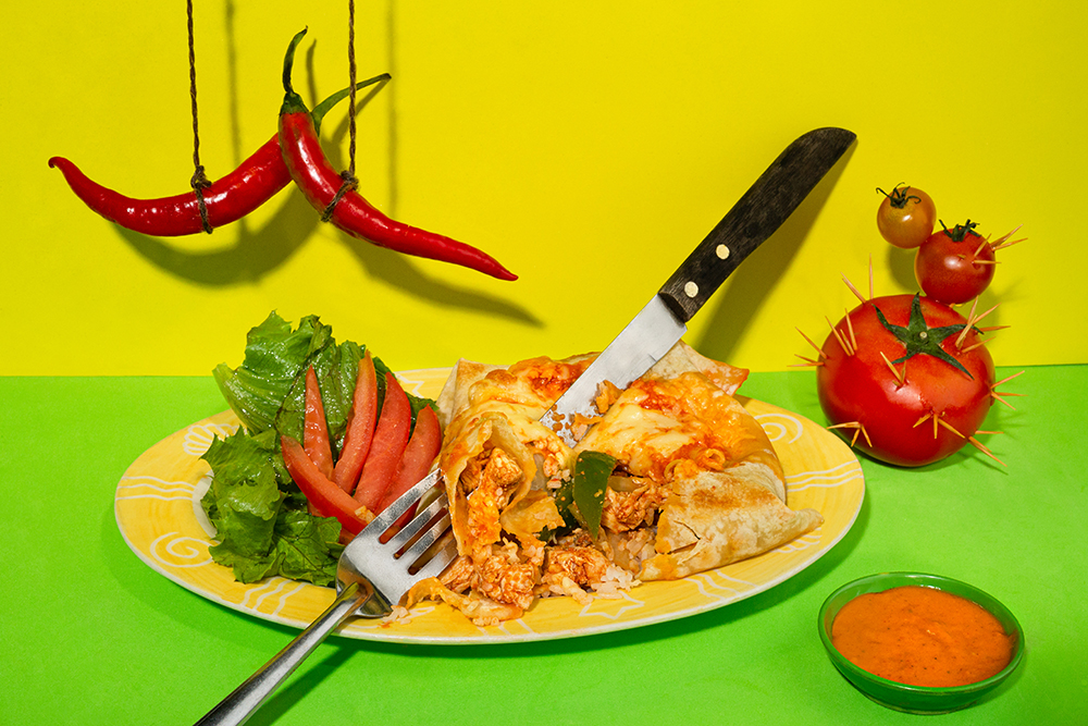 Mexican burrito, lavash with chicken, salad on plate with fol and knife, tomatoes like a cactus, red chilli peppers like mustach and Enchilada Sauce on multi colored tablecloth background. Copy space