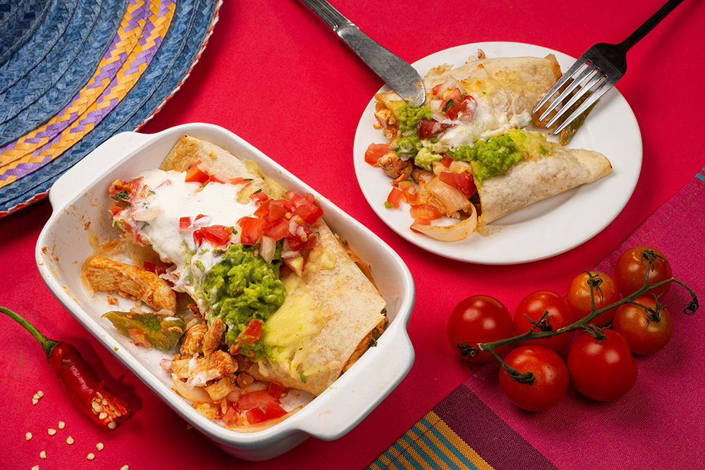 Mexican food. Cuisine of South America. Traditional dish of spicy chicken enchiladas with corn, beans, guacamole, tomatoes, chilli,. On a baking tray and part of it is  on plate, on on multi colored tablecloth background. Top view.