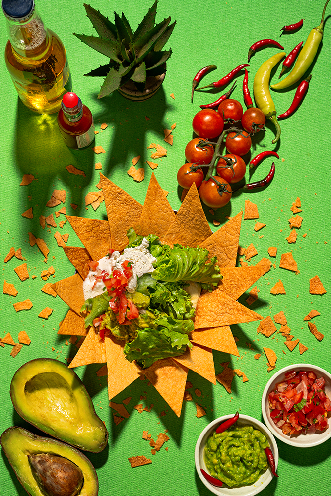 A plate of delicious tortilla nachos with melted cheese sauce, ground chicken meat, sour cream with guacamole dip and tomato on the table. Banner menu.
