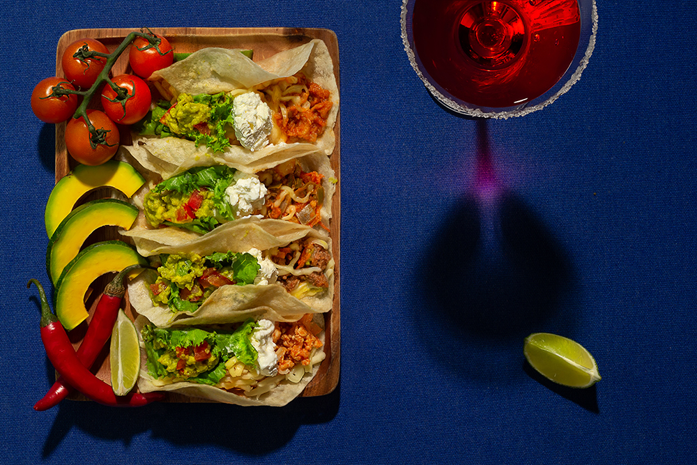 Mexican food - delicious taco shells with ground beef, chicken, vegetables and glass of Margarita over blue background Top view. Banner menu