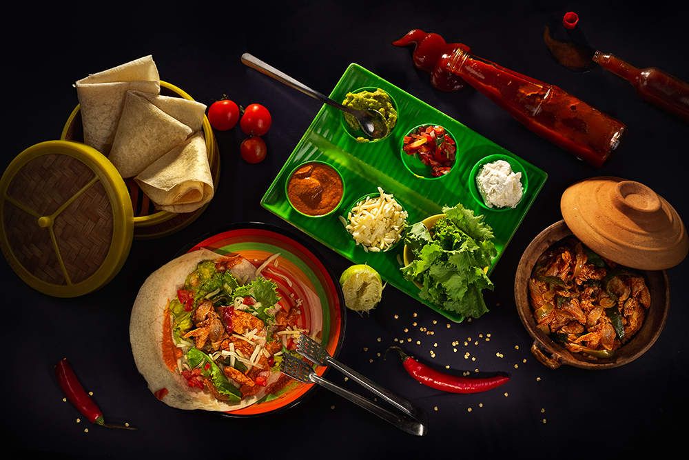 Spicy chicken, vegetables, sour cream, cheese, guacamole, Enchilada Sauce and corn tortillas fajitas in bamboo pancake basket on a dark background, top view. Delicious snack, tapas in mexican style